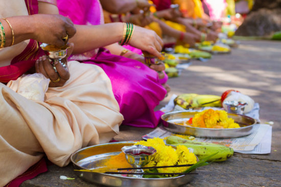 Hindu ladies peform a ritual offering to the Devi